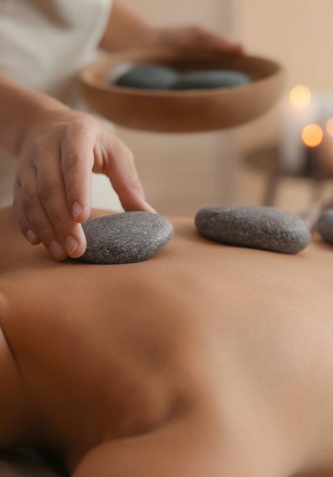 Beautiful Young Woman Getting Hot Stone Massage In Spa Salon